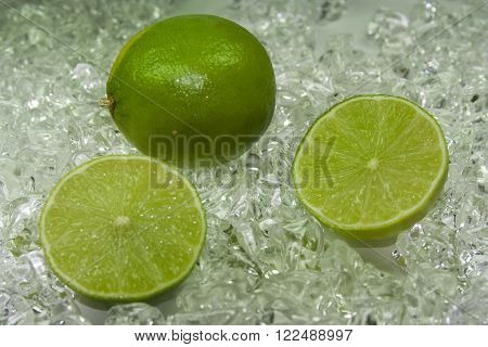 two fresh green  lime on cold ice ** Note: Shallow depth of field