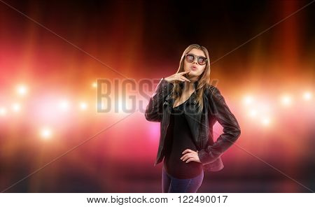 Sexy young woman in leather jacket and sunglasses is surrounded by care and camera flash. Celebrity, model, star.