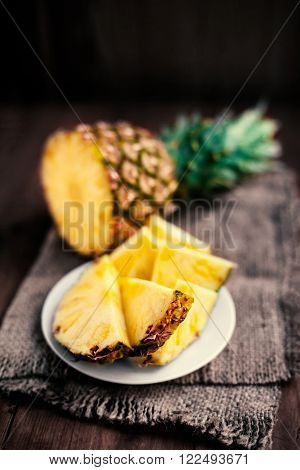 Pineapple tropical fruit / Ananas with slices over wooden table / Rustic country style