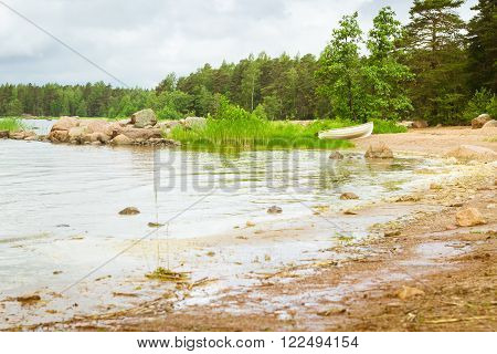 White rowing boat stands on a sandy shore in a quiet Bay of the Finnish Gulf. Area for summer camping in the woods. Hamina, Finland, Suomi