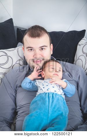 Young Father and His Little Baby Boy Together. Papa with His Cheerful Newborn on Sofa Taking Good Time. Domestic Family. Closeup Portrait of Dad and His Daughter Relaxing on Bed at Home Caring for Her