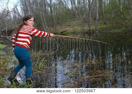 Tver, Russia - May 6 2006: Rural adolescent girl Tanya Shchegoleva 11 years old shod in rubber boots fishing in a small river using bamboo rods.