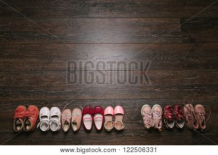 Old worn baby (child kid) shoes on the floor. sandals boots slippers sneakers top view. flat lay