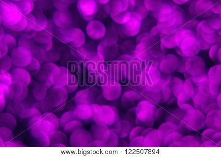 The photo shows a purple surface covered with glitter. Lens deliberately set beyond the point of focus to obtain a blur effect.