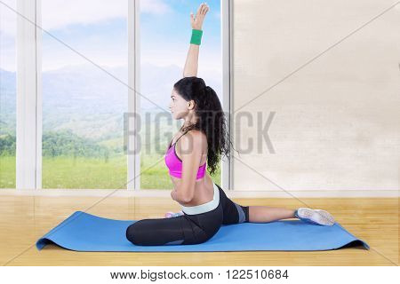 Picture of Indian young female athlete wearing sportswear and doing workout on the mat at home