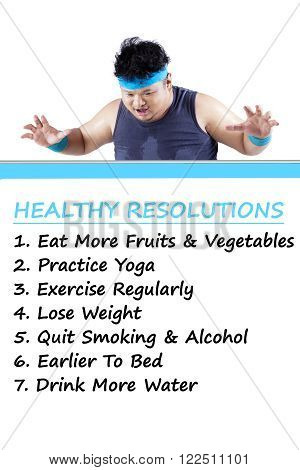 Overweight person wearing sportswear and looking at the list of healthy resolutions on the board