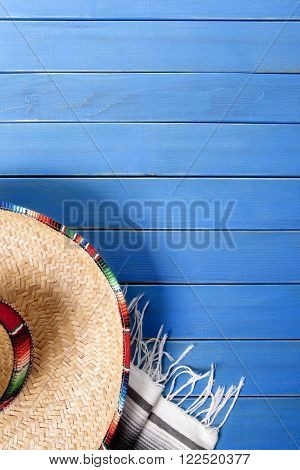 Mexican sombrero and traditional serape blanket laid on an old blue painted pine wood floor. Space for copy.