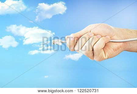 Internet cable in hand on blue sky background with cloud