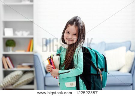 Little girl with green back pack holding stationery in living room
