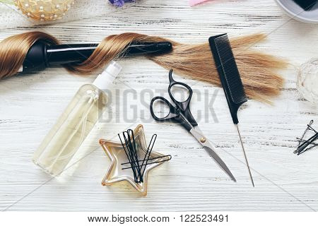 Strand of hair with flowers, barber equipment and tools on light wooden background poster