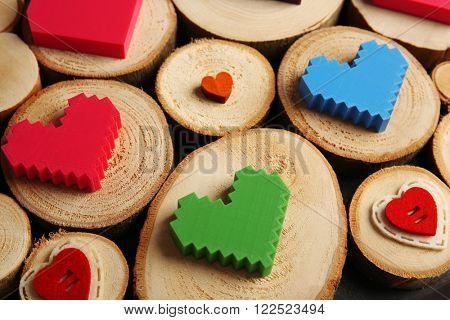 Plastic varicoloured hearts on wooden logs