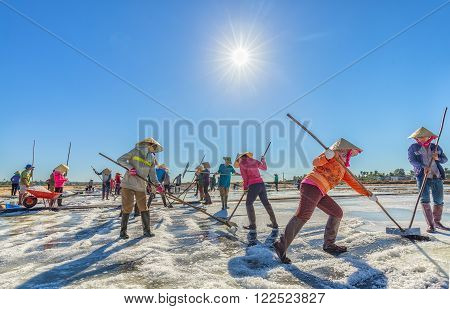 Binh Thuan, Vietnam - January 22nd, 2016: Close group of fishermen are raking salt in the sun rhythm Early harvest promises a lot of salt in the coastal countryside Binh Thuan, Vietnam