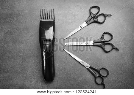 Barber set with hair trimmer and scissors on grey background poster
