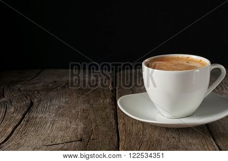 cup of coffee with thick of crema on wooden table on black background closeup with copy space. Coffee background