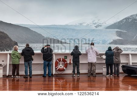 Amilia Glacier, South Patagonia, Chile, - December 8, 2012: Passengers on board the cruise ship Veendam viewing beautiful glacier. Taken at the Sarmiento Channel, Chile on a overcast rainy day. Amalia Glacier, also known as Skua Glacier, is a tidewater gl