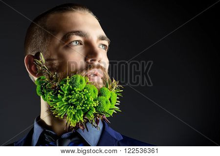 Portrait of a handsome man with a beard of green flowers. Men's beauty. Barbershop. Copy space.