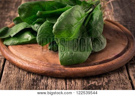 Bunch Of Fresh Spinach With Roots Over Old Wooden Surface. Dark Rustic Style