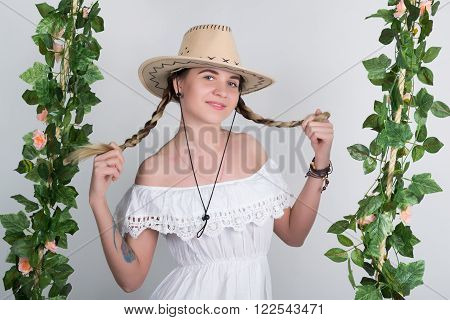 Beautiful young leggy blonde in a little white dress and white cowboy hat on a swing, wooden swing suspended from a rope hemp, rope wrapped vine and ivy. she keeps herself pigtails.