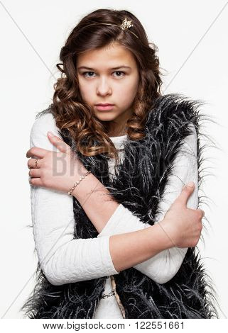 Gestures. Teenagers. Young girl in a light shirt and a fuzzy vest performing chill and discomfort, she freezes, isolated on white background