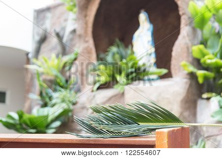 Closeup Of Palm Leaf On Pews With De-focused Grotto