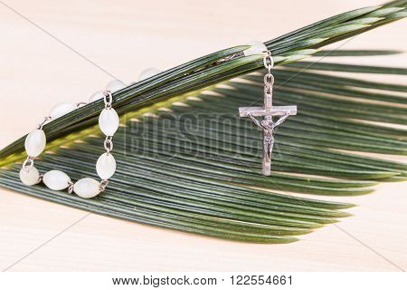 Closeup of Holy Catholic rosary with crucifix and beads on palm leaf poster