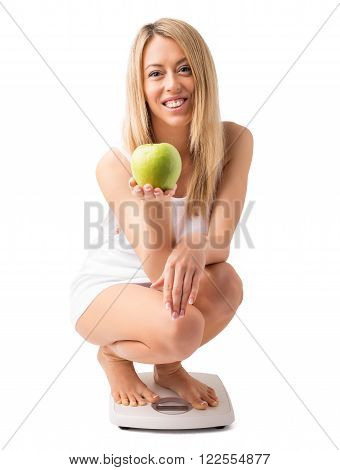 Woman on weight scale holding apple and smiling