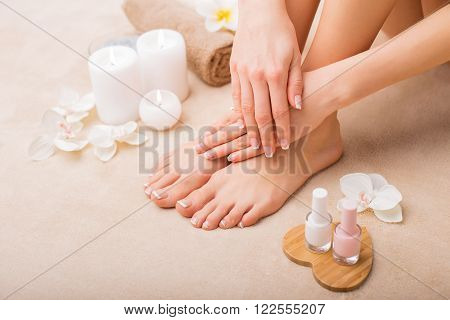 Woman at spa with done manicure and pedicure poster