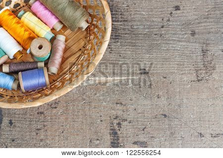Bobbins with thread. Old sewing tools on the old wooden surface. Vintage background