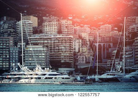 Monte Carlo, Monaco - September 20, 2015: yachts and sailboats modern vessels at moorage in sea port on sun set light shot against mountains on cityscape background, horizontal picture