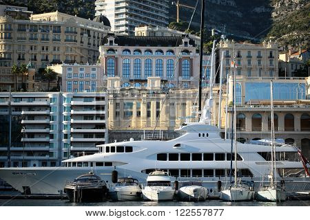 Monte Carlo, Monaco - September 20, 2015:  small motor boats and yachts against luxury large vessel ship at moorage in port inshore on sunny summer day on cityscape background, horizontal picture