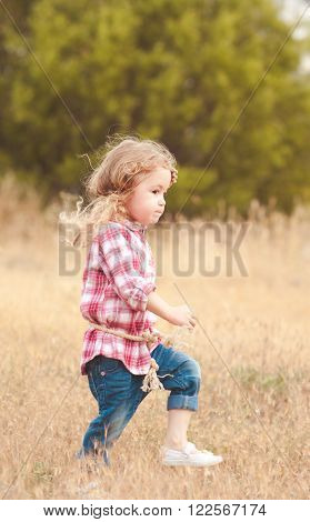 Stylish kid girl 2-3 year old walking in meadow. Childhood. Country side.