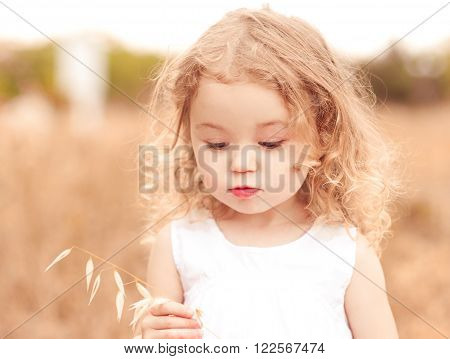 Little funny girl 2-3 year old playing in meadow. Cute child. Childhood.