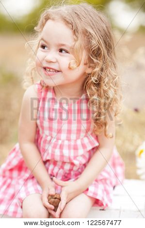 Funny baby girl 2-3 year old  sitting in meadow outdoors. Laughing child. Looking away. Childhood.