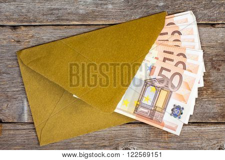 Golden envelope with Euro bills over wooden background
