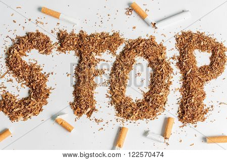 Broken cigarettes and tobacco on white background. Stop smoking now