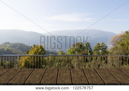 metal banister of balcony with mountain view (blur background with wood table top for display or montage your product)