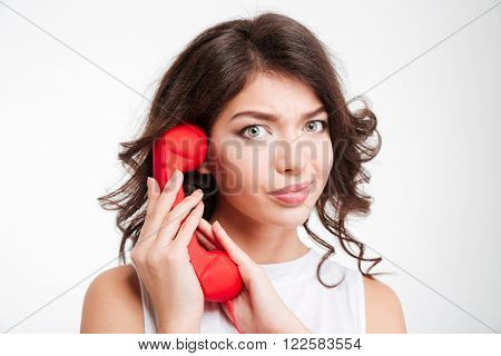 Young woman covering microphone on phone tube and looking at camera isolated on a white background