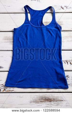 Woman's blue tank top. Blue tank top on shelf. Simple top for warm season. Clothes shop's showcase.