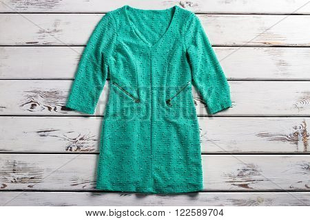 Turquoise dress with pockets. Dress laying on wooden table. V-neck turquoise dress. Woman's long sleeve garment.