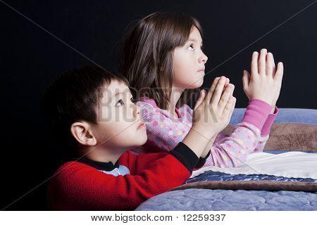Siblings say bedtime prayers.