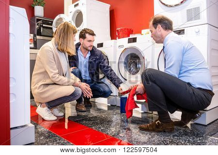 Full length of salesman explaining product to customers in washing machine department of hypermarket