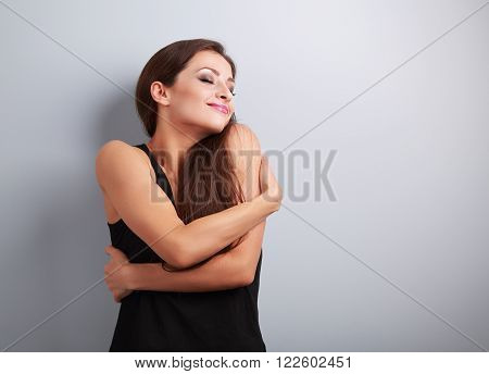 Happy strong sporty woman hugging herself with natural emotional enjoying face. Love concept of yourself body poster