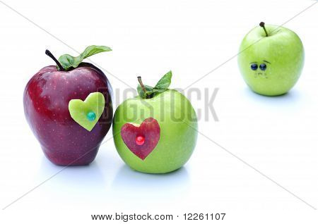 A couple of apples lovers embrace in front of lonely apple