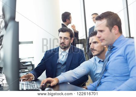 Business team working in corporate office. Businessmen trading stocks. Stock traders looking at data on multiple computer screens. Business success concept.