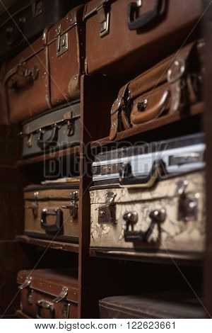 Selective focus photo of vintage suitcases stacked on the shelves close up view 1
