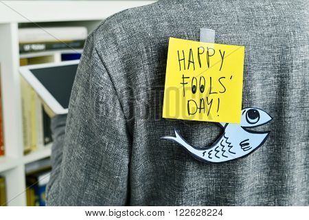 closeup of a young man with a paper fish and a note with the text happy fools day attached with tape to his back poster