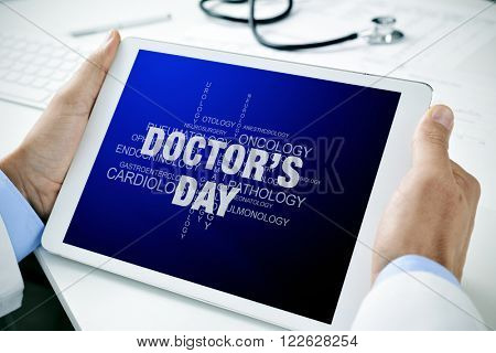 closeup of a doctor man sitting at his office desk holding a tablet computer with a tag cloud of different medical specialties and the text doctors day in its screen