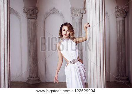 Portrait of young sexy woman in a white dress, in the luxurious hall with columns