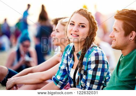 Group of teenagers at summer music festival, sitting on the ground , teenage girl with braided hair, checked shirt