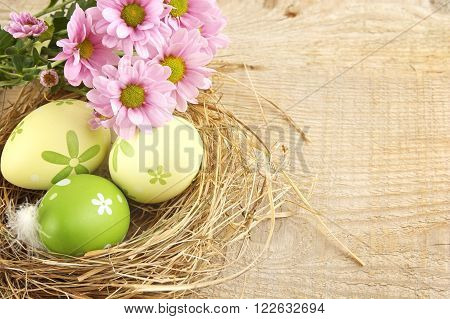 Easter Eggs In The Nest With Flowers On Wooden Plank